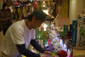 原宿店店長のたかさんが、商品を陳列している場面。